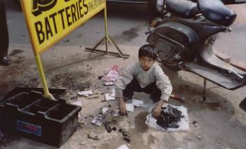 Hazardous battery recycling on the streets of New Delhi. A child disassembles a spent truck battery on the sidewalk to sell lead to unregistered recycling units.