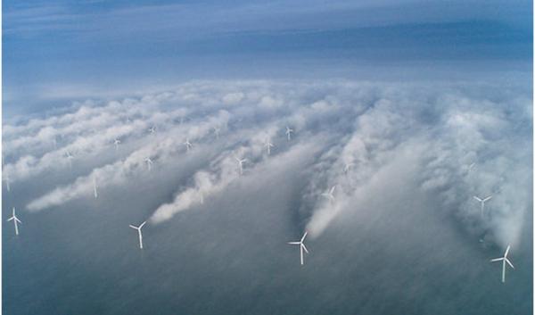 Windustrieterrein op zee met windschaduw molens die door vermenging luchtlagen condensatiesporen geven