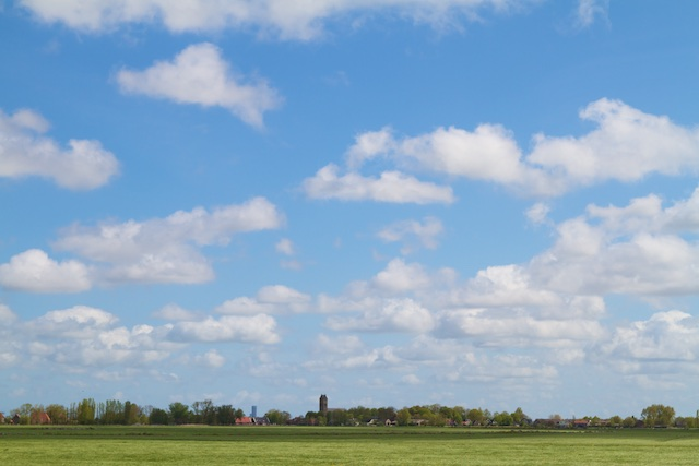 Jorwerd ligt als eiland in eeuwenoud zeeklei-krekenland waar de Middelzee in lag. Nu in gifgroene agrozee, met Mammon-toren op achtergrond van Avero