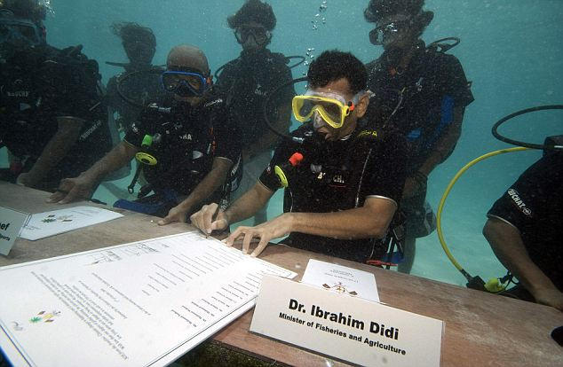 Maldivian Minister of Fisheries and Agriculture Ibrahim Didi signs a document calling on all countries to cut down their carbon dioxide emissions ahead of a major U.N. climate change conference in December in Copenhagen, in Girifushi, Maldives, Saturday, Oct. 17, 2009. Government ministers in scuba gear held an underwater meeting of the Maldives' Cabinet to highlight the threat global warming poses to the lowest-lying nation on earth. Maldivian President Mohammed Nasheed led Saturday's meeting around a table on the sea floor, 20 feet (6 meters) below the surface, with ministers communicating using white boards and hand signals. (AP Photo/Mohammed Seeneen)