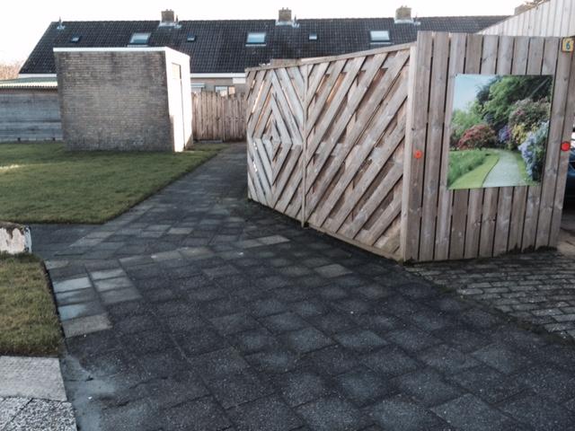 Een afbeelding van ironie? Spandoek groene tuin in tegeltreurnis met intratuin-kasteelmuren